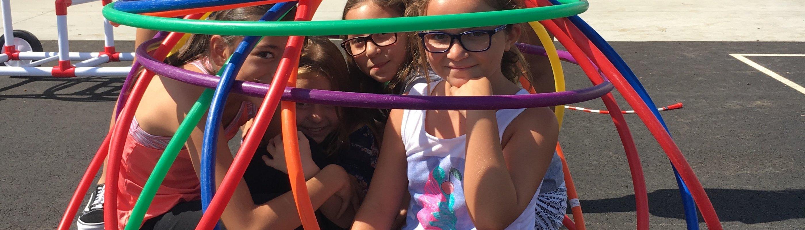Girls engineering a hoola hoop ball